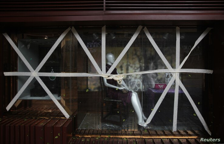 Display panels of a store at Tsim Sha Tsui shopping district are seen taped together as part of safety measures in preparation for Typhoon Vicente, Hong Kong, July 24, 2012.