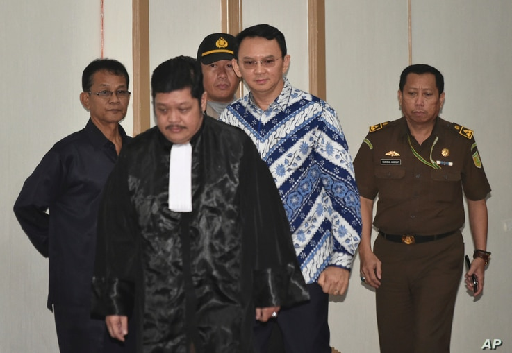 "Jakarta Governor Basuki ""Ahok"" Tjahaja Purnama, center, is escorted by prosecutors as enters the court room for his sentencing hearing in Jakarta, Indonesia, May 9, 2017."