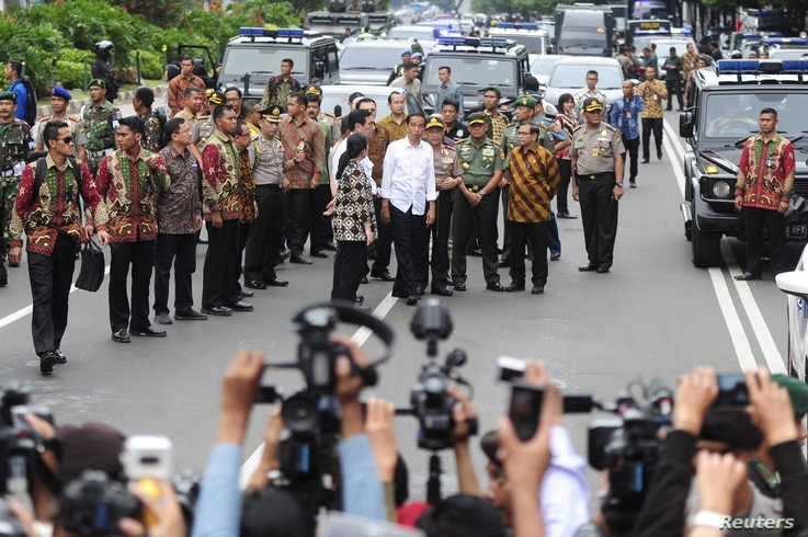 Indonesian President Joko Widodo, center, in white shirt, visits the site of a bomb blast at Thamrin business district in Jakarta, Jan. 14, 2016.
