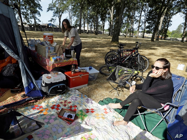 Hilary O'Hollaren, right, sits in the early morning sun as Rory O'Hollaren prepares breakfast as they camp near the state fairgrounds in preparation for the Aug. 21, 2017, solar eclipse in Salem, Ore.