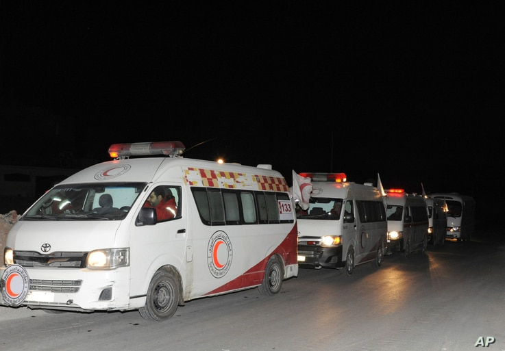 FILE - In this photo released by the Syrian official news agency SANA, ambulances of the Syrian Arab Red Crescent line up during a mission to evacuate sick and wounded people from Eastern Ghouta, near Damascus, Syria, Dec. 28, 2017.