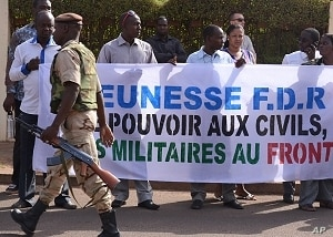 A soldier walks past Malians protesting the junta's arrest of several prominent figures, in front of the hotel where interim president Dioncounda Traore is staying. The sign reads in part, 'Military to the front lines, power to civilians'. Bamako, Ap...