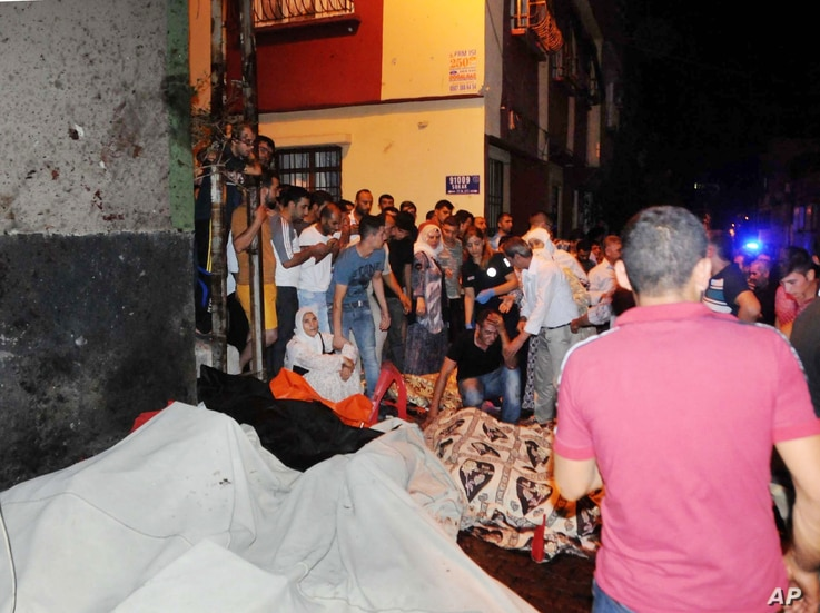 People react after an explosion in Gaziantep, southeastern Turkey, Aug. 21, 2016. Gaziantep province Gov. Ali Yerlikaya said the deadly blast, during a wedding near the border with Syria, was a terror attack.