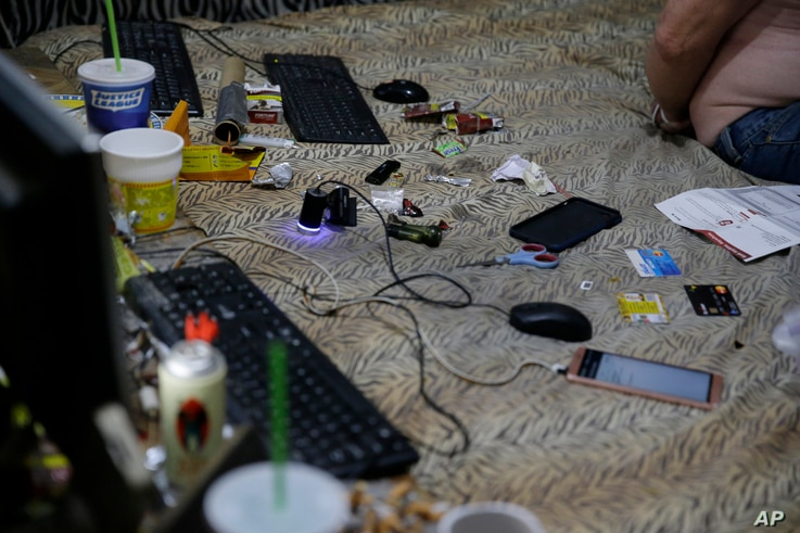 Smartphones, credit cards, food wrappers and cigarettes are found on the bed of suspected child webcam cybersex operator, David Timothy Deakin, from Peoria, Ill., during a raid in Mabalacat, Philippines, April 20, 2017.