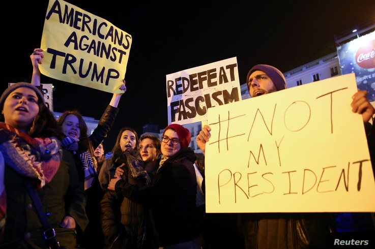 Anti-Trump protesters hold banners during a demonstration at Puerta del Sol Square in Madrid, Spain, Dec. 2, 2016.
