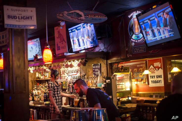 Bartenders work at McGarveys Bar in Manchester, N.H., as the Republican presidential debate is shown on televisions