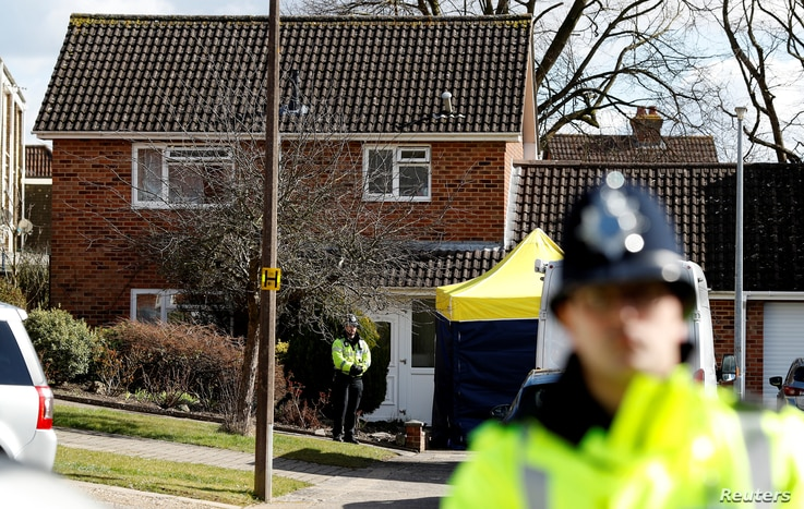 Police officers stand guard outside the home of Sergei Skripal in Salisbury, Britain, March 8, 2018.