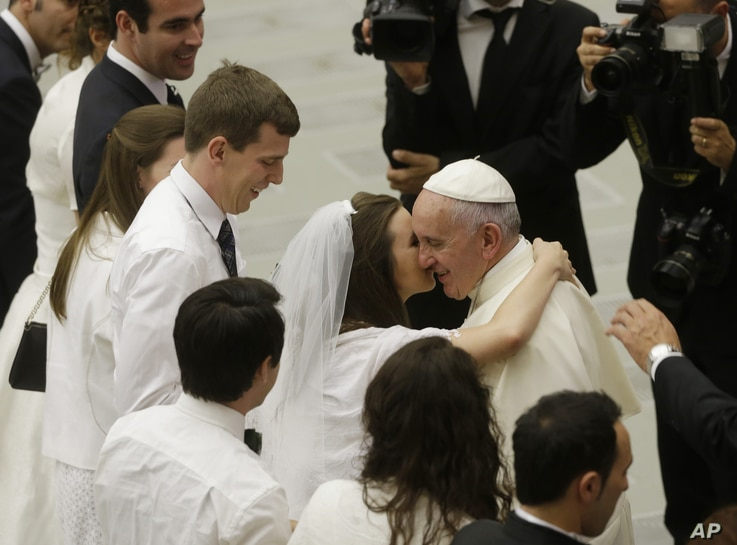Pope Francis greets newlyweds during the general audience at the Vatican, Aug. 5, 2015. Pope Francis says divorced Catholics who remarry and their children deserve better treatment from the Catholic church.