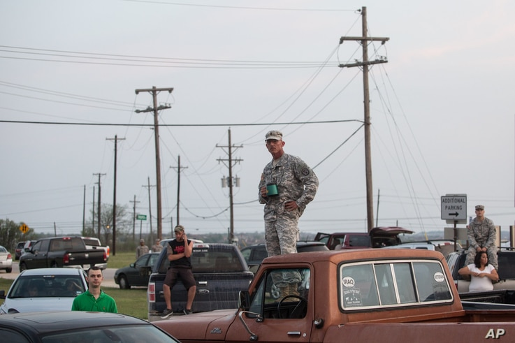 Military personnel and civilians wait in a parking lot outside the Fort Hood military base for updates about the shooting that occurred inside, April 2, 2014.