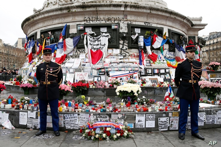 French honor guards stand next to the monument at Place de la Republique in Paris, where people laid candles cards and flags during a ceremony to honor the victims of the Islamic extremist attacks, Jan. 10, 2016.