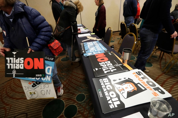 Signs opposing offshore oil drilling are distributed, March 5, 2018, at a hearing in Olympia, Wash., organized by a coalition of environmental groups opposed to the Trump administration's proposal to expand offshore oil drilling off the Pacific North...