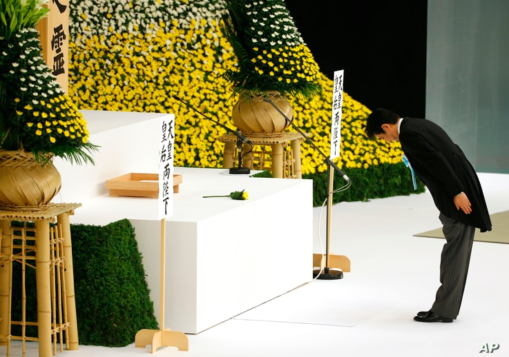 Japanese Prime Minister Shinzo Abe bows before the main altar decorated with huge bank of chrysanthemums as he offers prayers for the war dead during a memorial service at Nippon Budokan martial arts hall in Tokyo, Aug. 15, 2015. J