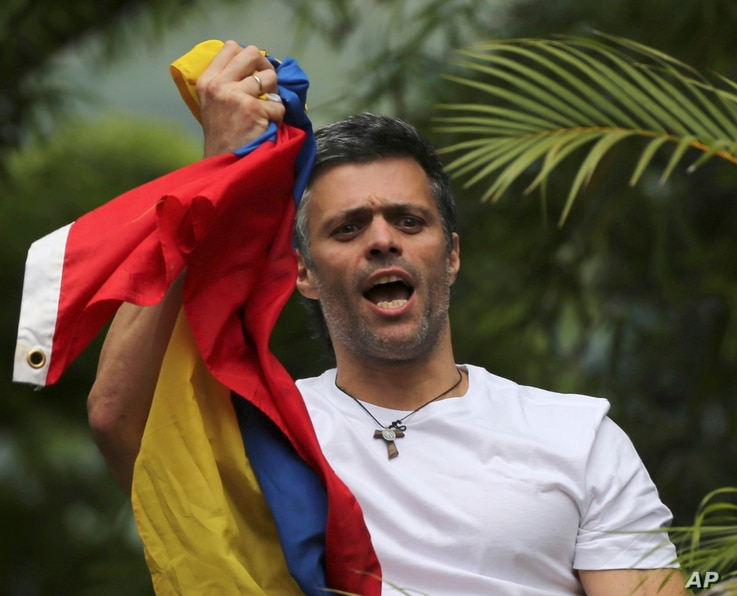 FILE - Venezuela's opposition leader Leopoldo Lopez holds a national flag as he greets supporters outside his home in Caracas, Venezuela, following his release from prison.