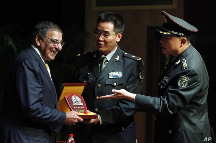 U.S. Defense Secretary Leon Panetta, left, receives a plaque after he addresses cadets at the PLA Engineering Academy of Armored Forces in Beijing, China, September 19, 2012.