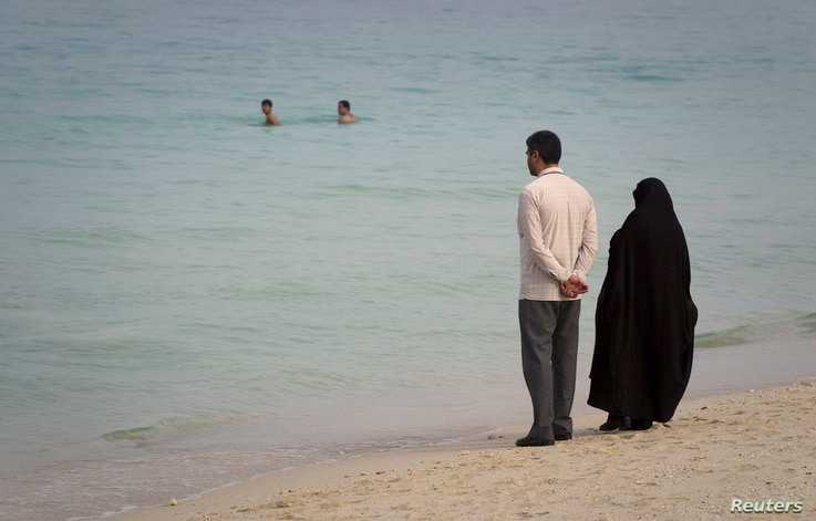 FILE - A couple watches swimmers as they stand on the beach of Kish Island, 1,250 kilometers (777 miles) south of Tehran, April 26, 2011.