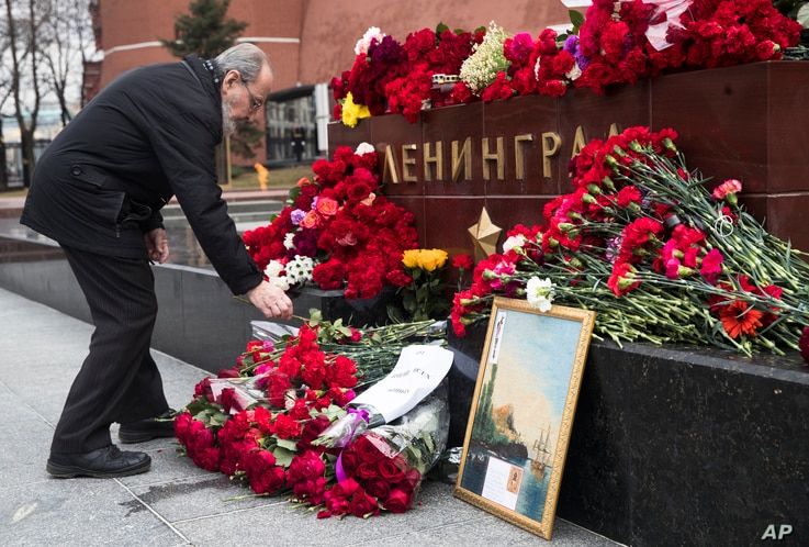 A man lays flowers in memory of victims killed by a bomb blast in a subway train in St. Petersburg, at the memorial stone with the word Leningrad (St. Petersburg) at the Tomb of Unknown Soldier, in front of the Kremlin wall in Moscow, Russia, April 4...