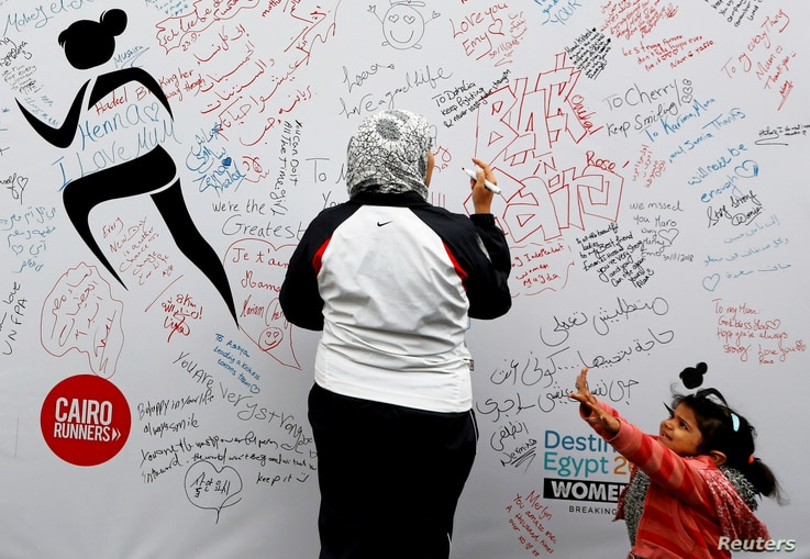 A woman, with her daughter, writes a message of support during the first Egyptian womens' race, to raise awareness about violence against women, in Cairo, Egypt, Nov. 30, 2018.