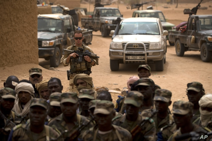 FILE - A French soldier stands watch behind Malian soldiers during a visit by the head of France's Operation Serval and Mali's army chief of staff to a Malian army base in Kidal, Mali.