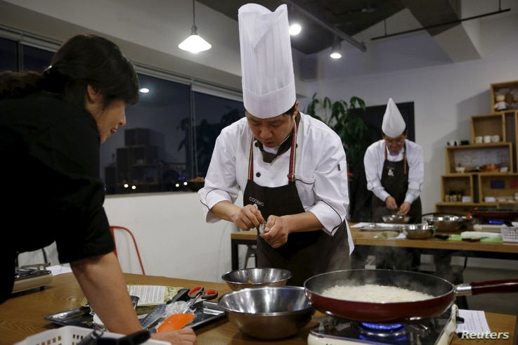 Lee Jin-soo (C), 53, prepares an ear shell at Happy Guys Cooking Class in Seoul, South Korea, July 31, 2015.
