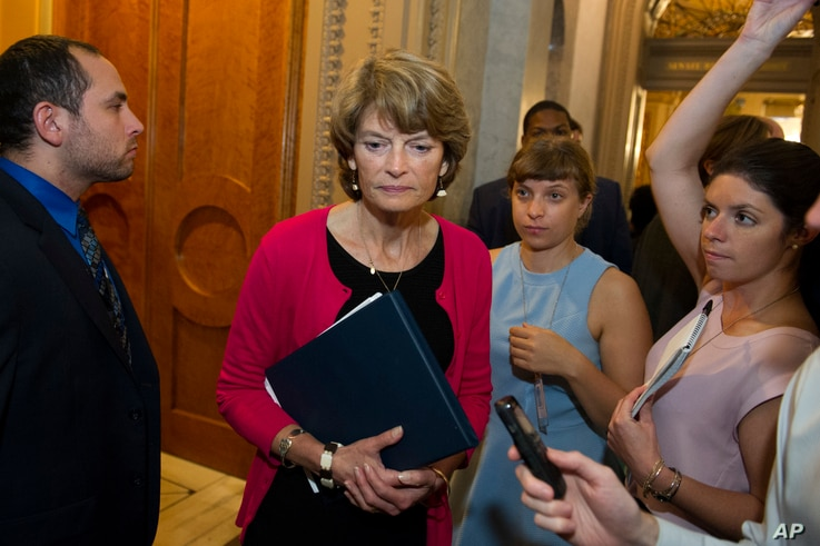 FILE - In this July 28, 2017, file photo, Sen. Lisa Murkowski, R-Alaska, passes reporters as she leaves the Senate chamber on Capitol Hill in Washington. Conservatives across the country warned that the GOP-led Congress could not abandon its pledge t...