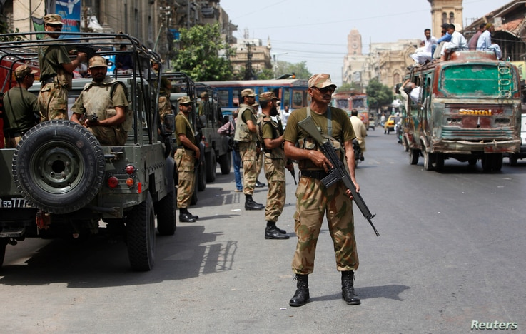Paramilitary soldiers stand guard along a road outside of the district city court in Karachi, Pakistan, May 10, 2013.