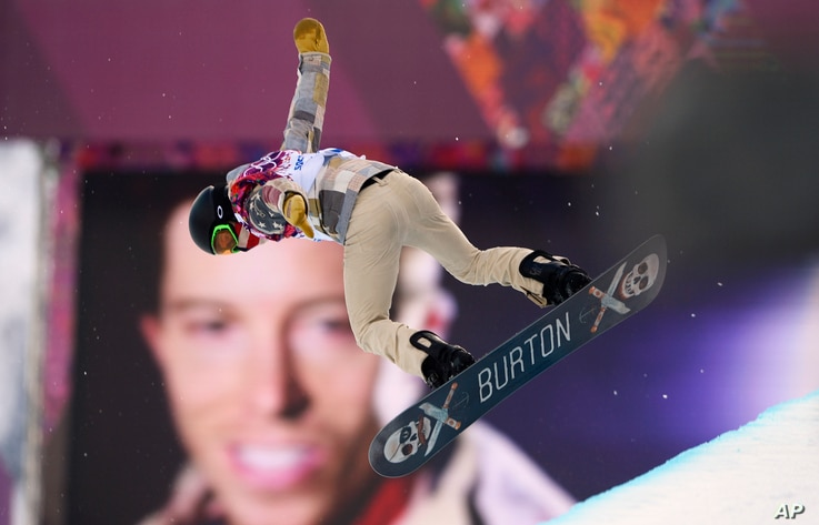 Shaun White of the U.S. performs a jump near a picture of himself during the men's snowboard halfpipe qualification round at the 2014 Sochi Winter Olympic Games in Rosa Khutor February 11, 2014. REUTERS/Dylan Martinez (RUSSIA  - Tags: SPORT SNOWBOARD...