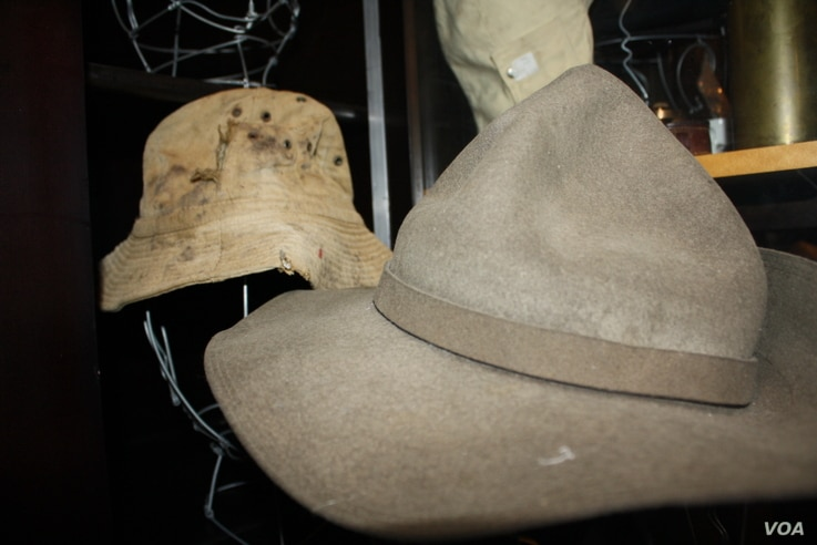 The War Store has hundreds of hats and helmets from battlefields... Including the hat in the background that belonged to a soldier killed in conflict in what's now Namibia in the 1980s. (D. Taylor/VOA)