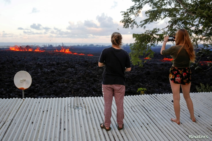 Jolon Clinton, 15, (L), and her sister, Halcy, 17, take photos of a fissure near their home on the outskirts of Pahoa during ongoing eruptions of the Kilauea Volcano in Hawaii, U.S., May 14, 2018.