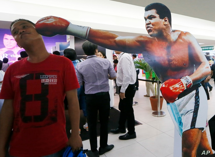 A Filipino fan poses before a standee of Muhammad Ali at an exhibit of photos and memorabilia launched last week to pay tribute to Muhammad Ali, in Quezon city, Philippines, June 10, 2016.