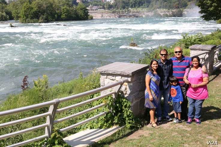 "Vikas and Madhavi Vijay drove from Cleveland, Ohio, to Niagara Falls State Park to show their son and visiting parents ""the pressure of the waterfalls"" and experience the 'Maid of the Mist' boat ride. (R. Taylor/VOA)"