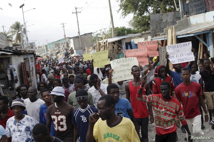 Protesters march during a demonstration against the government in Port-au-Prince, Haiti, Jan. 25, 2016.
