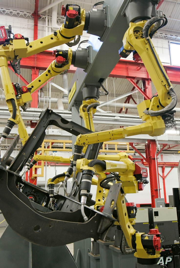 FILE - Arms from a robotic welder simulate welds on a piece of metal in Euclid, Ohio. Today's welding technicians operate robots that can do welds quicker than humans and with more precision.