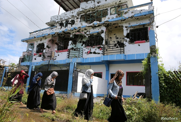 Residents who returned from evacuation centers walk past a bullet-ridden house believed to have been rented by pro-Islamic State militant group leaders Isnilon Hapilon and Omar Maute before their attack on the region, in Basak, Malutlut district in M...