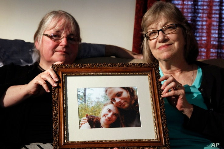 FILE- Linda Boyle, left, and Lyn Coleman hold a photo of their married children, Joshua Boyle and Caitlan Coleman, June 4, 2104, who were kidnapped by the Taliban in late 2012.