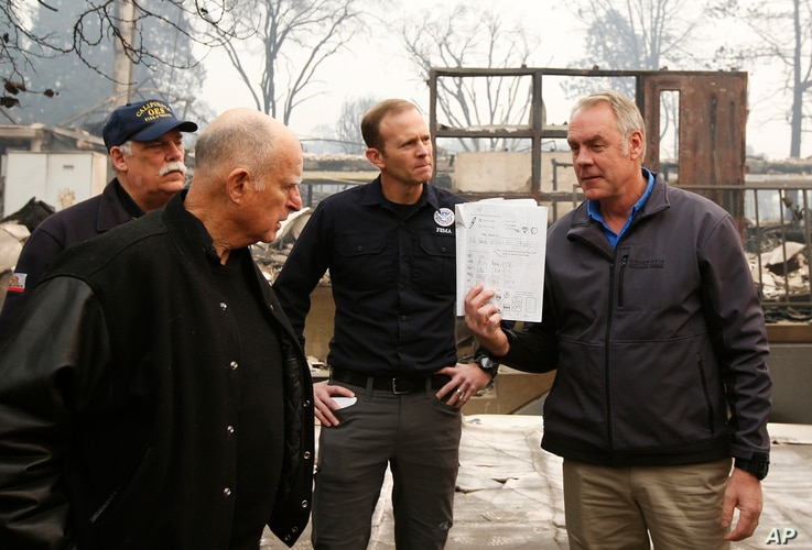 California Gov. Jerry Brown, (2-L), looks at a student work book, held up by Interior Secretary Ryan Zinke, that was found during a tour of the fire-ravaged Paradise Elementary School Wednesday, Nov. 14, 2018, in Paradise, California.