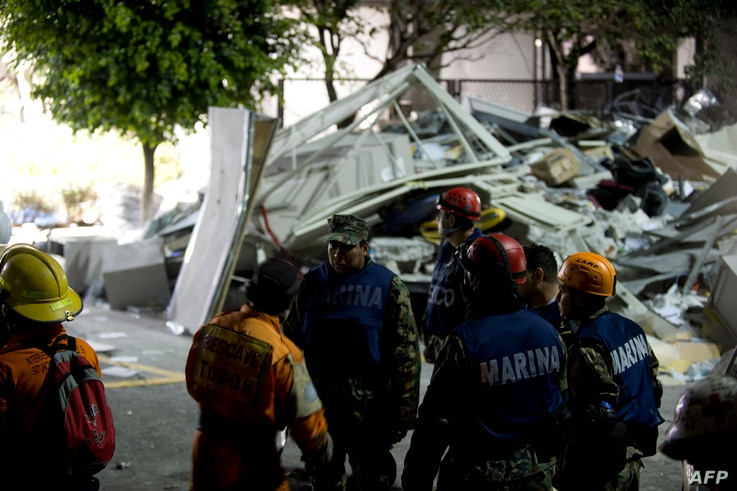 Rescue workers search for victims at the headquarters of state-owned Mexican oil giant Pemex in Mexico City following a blast inside the building, January 31, 2013.