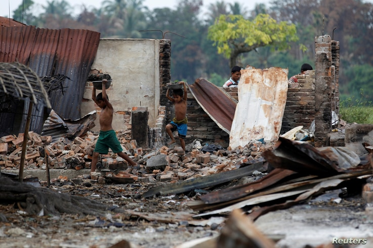 Children recycle goods from the ruins of a market which was set on fire at a Rohingya village outside Maugndaw in Rakhine state, Myanmar, Oct. 27, 2016.