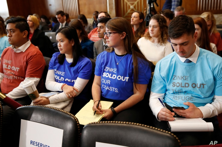 Attendees of a Senate Committee on Energy and Natural Resources committee hearing wear t-shirts protesting Interior Secretary Ryan Zinke, as he testifies before the committee about the President's Budget Request for Fiscal Year 2019, March 13, 2018, ...