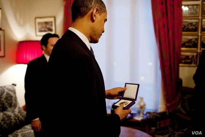 President Barack Obama looks at the Nobel Peace Prize medal for the first time at the Norwegian Nobel Institute in Oslo, Norway. December 10, 2009. (White House/Pete Souza)
