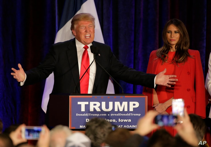 Republican presidential candidate, businessman Donald Trump speaks as his wife, Melania, watches at his caucus night rally in West Des Moines, Iowa, Feb. 1, 2016.