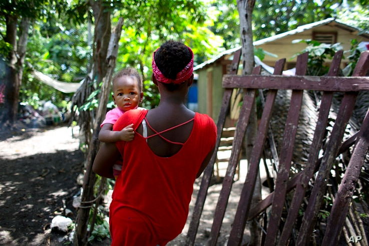 Janila Jean, 18, carries her daughter as she walks to her friend's house before an interview in Jacmel, Haiti, Aug. 15, 2016.