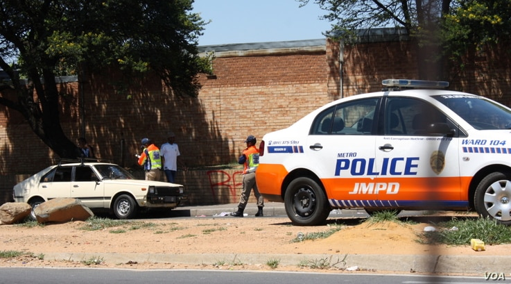 Traffic police fine a motorist in Johannesburg. Robert van Rensburg says if they stop him for drunken driving, he simply bribes them to let him go. (D. Taylor/VOA)