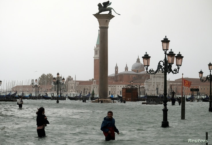 People walk in flooded Saint Mark Square during a period of seasonal high water in Venice, Italy, Oct. 29, 2018.
