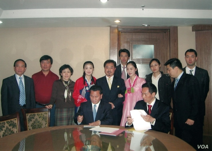 Ri Jong Ho, seated at left, seals a deal on North Korea's oil exploration with a Hong Kong international oil company in November 2006.