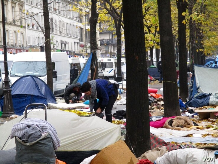 Local residents clearing up the detritus of a dismantled tent camp in northern Paris, Nov. 2016. ( VOA / L.Bryant)