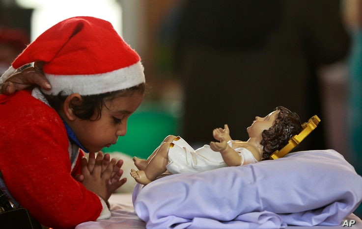 An Indian girl child offers prayers near an idol of baby Jesus on the occasion of Christmas at Saint Mary's Garrison Church in Jammu, India, Dec. 25, 2016.