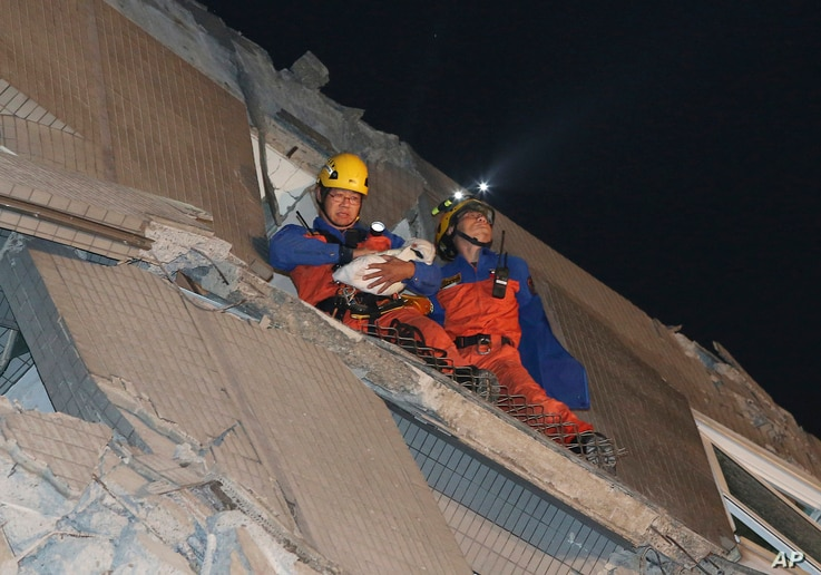Rescue workers carry a baby swaddled in a cloth from the rubble of a toppled building after an earthquake in Tainan, Taiwan, Feb. 6, 2016.