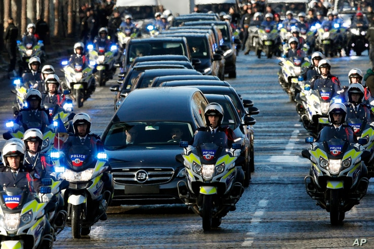 A motorcycle parade follows the hearse carrying the casket of French rock star Johnny Hallyday, down the Champs-Elysees avenue in Paris, Saturday, Dec.9, 2017.