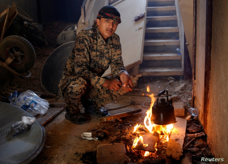 A Syrian Democratic Forces (SDF) fighter prepares tea in house in Raqqa, Syria, June 27, 2017.