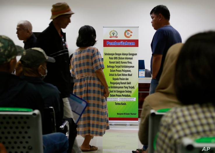 FILE - Patients wait near a banner informing of a delay in service due to a cyberattack at the Dharmais Cancer Hospital in Jakarta, Indonesia, May 15, 2017.